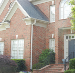 the-new-gutters-and-downspouts-are-attractively-and-professionally-installed-on-this-impressive-brick-home